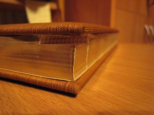 Книга с золотыми страницами на столе в закрытом виде