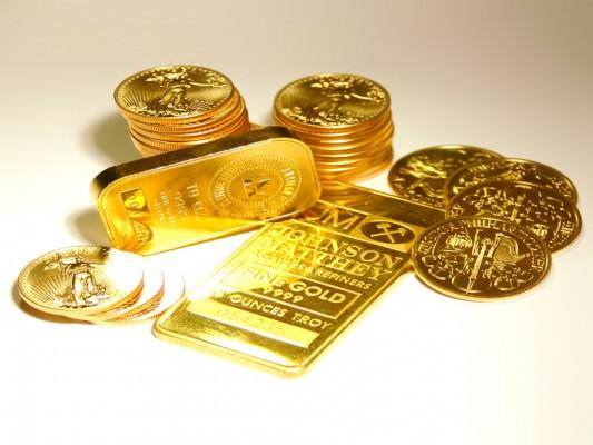 Золотой слиток и золотые монеты на белом фоне