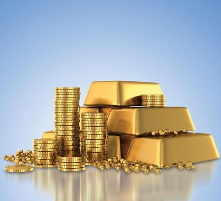 Стопки золотых слитков и монет на голубом фоне