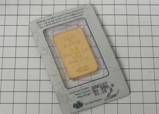 Золотой слиток в оправе на фоне белой плитки