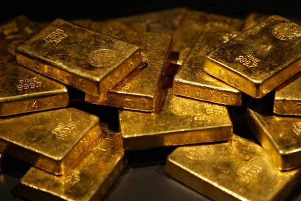 Золотые слитки в хаотичном порядке на чёрном фоне