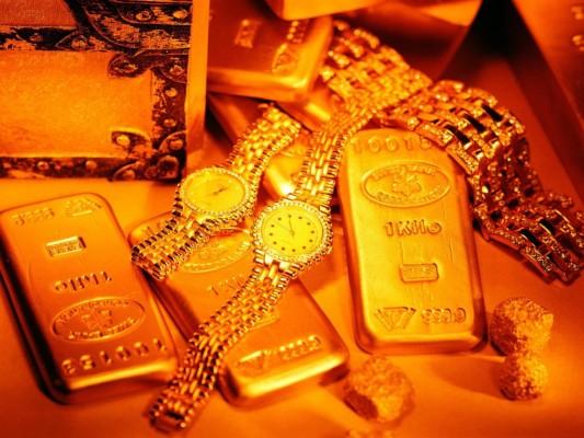 Груда золотых слитков и изделий из золота