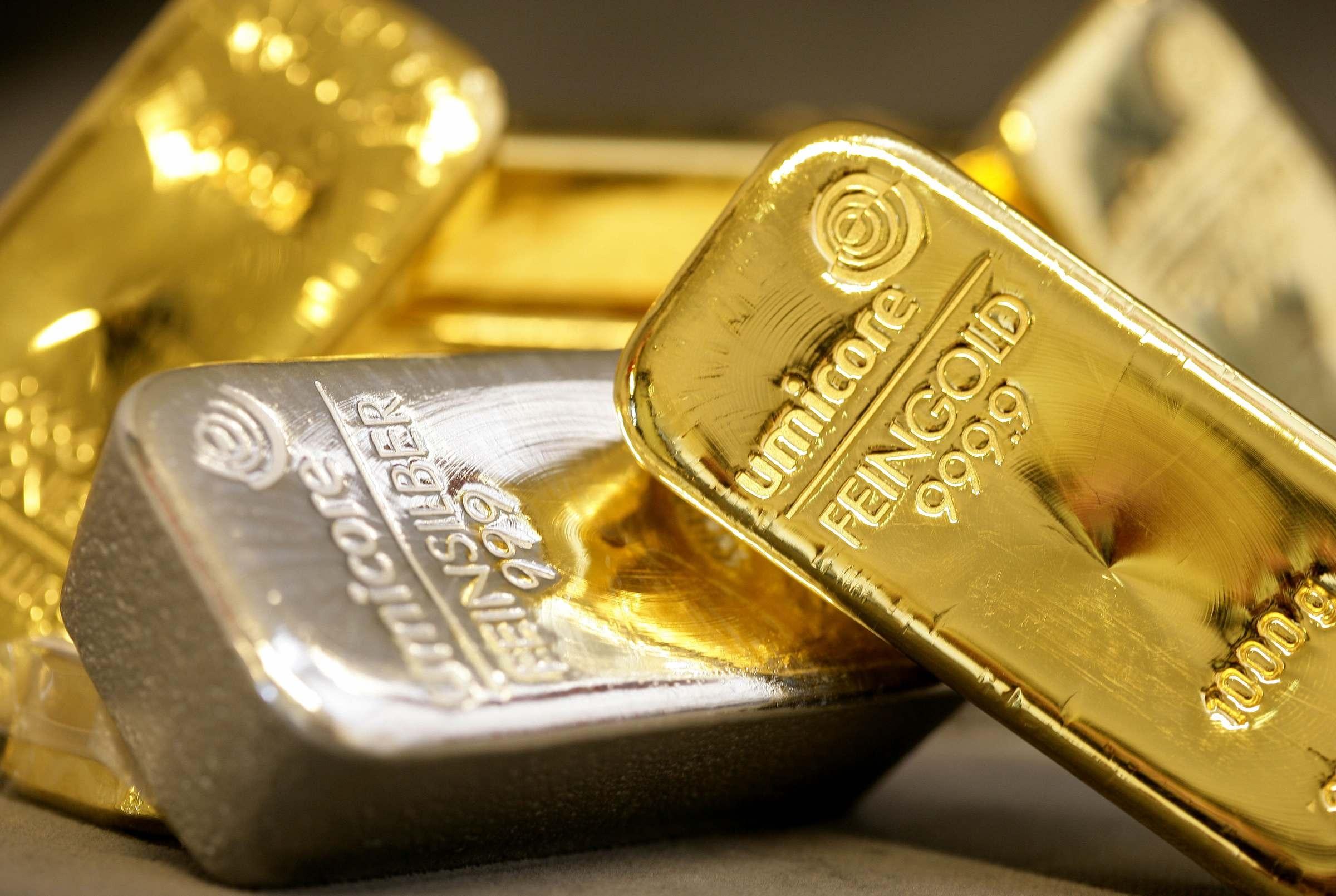 Золотой слиток, расположенный на фоне серебрянного