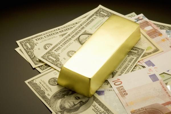 Слиток золота, доллары и евро