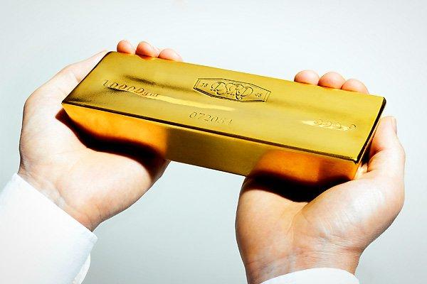 Золотой слиток в руках на белом фоне