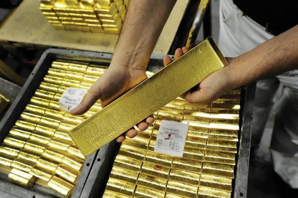 Сложенные золотые слитки и один в руках