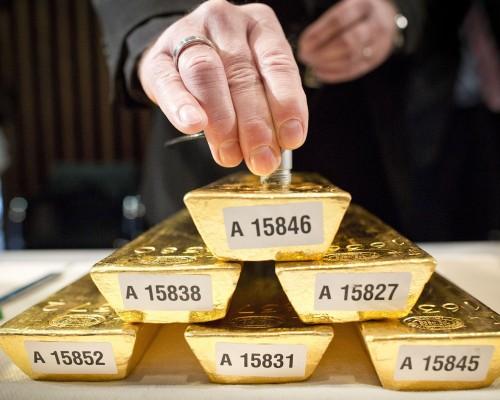 Стопка из 5 золотых слитков и рука над ними