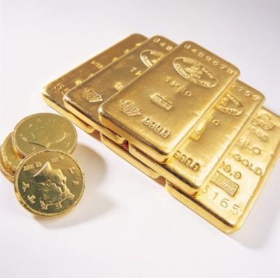 Золотые слитки и золотые монеты на белом фоне