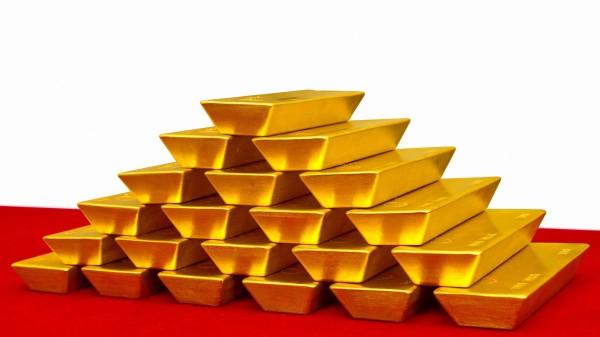 Аккуратно сложенные золотые слитки на красной поверхности