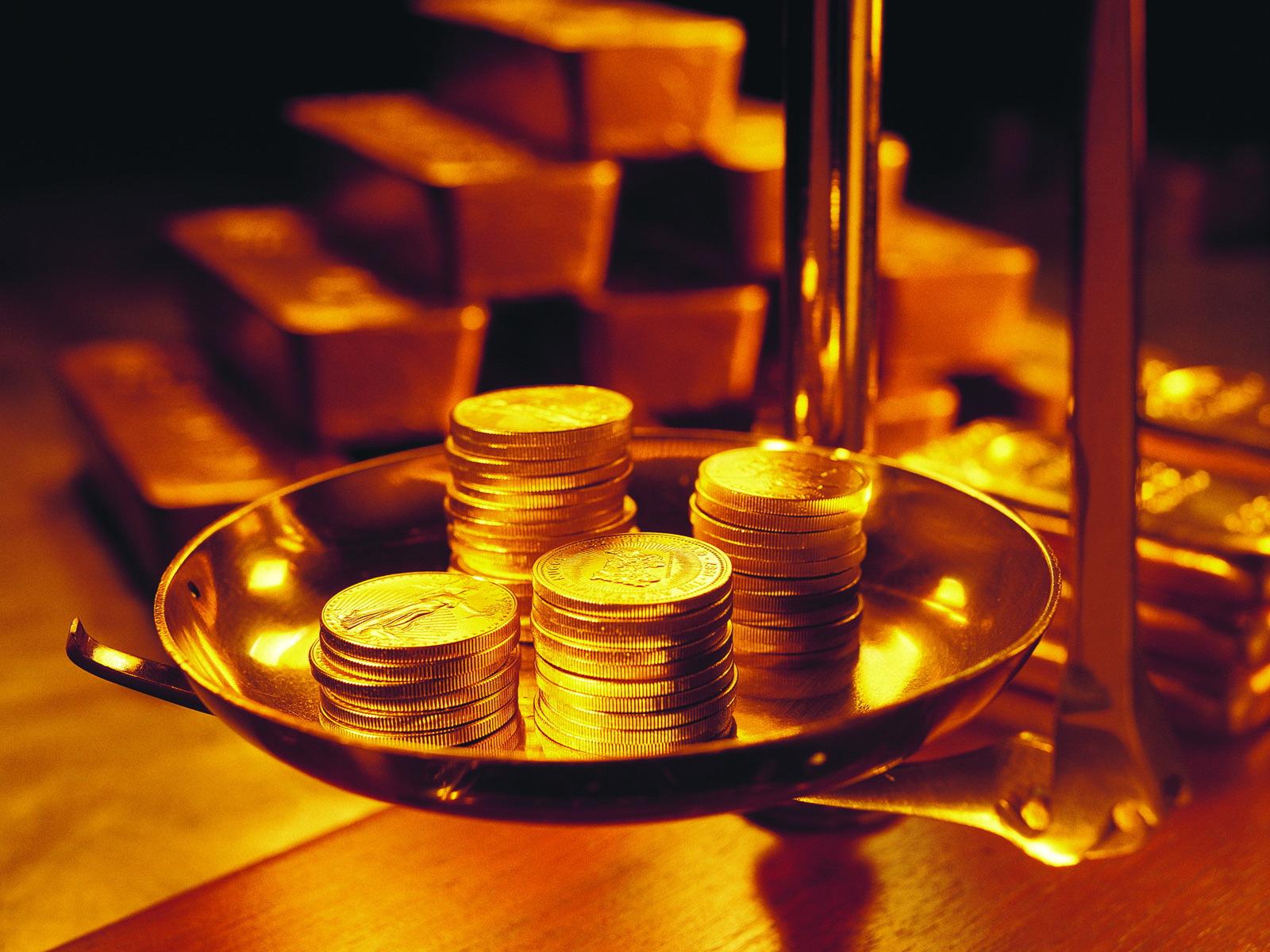 На переднем плане - чаша весов с золотыми монетами, на заднем - золотые слитки