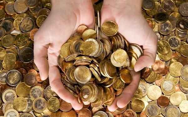 Монеты в ладонях на фоне груды монет