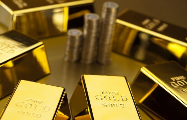 Золотые слитки и 3 стопки монет на золотом фоне
