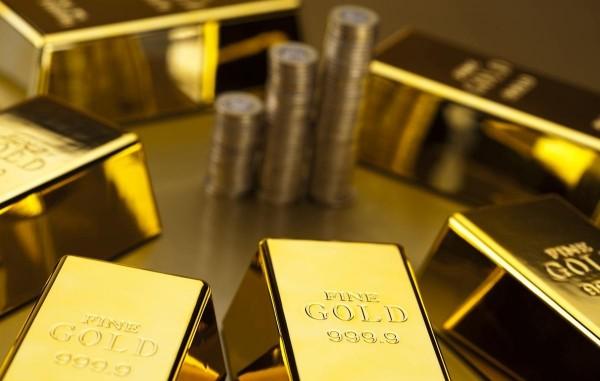Золотые слитки (крупным планом) вокруг стопки золотых монет)