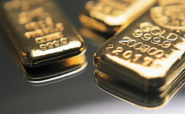 Три золотых слитка на сером фоне