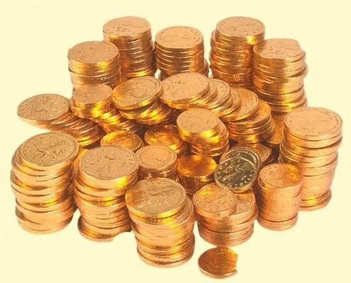 Стопки монет вокруг груды монет на светло-золотистом фоне