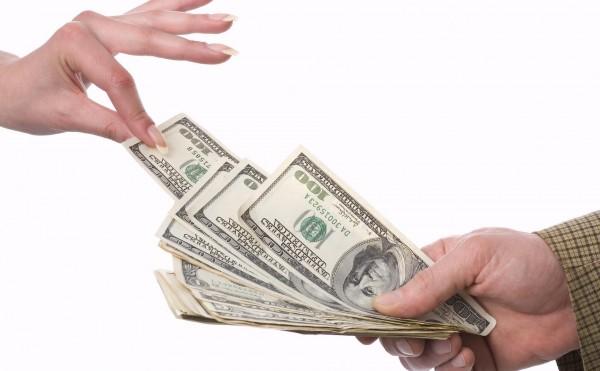Рука, дающая купюры долларов США и рука, берущая эти купюры - на белом фоне