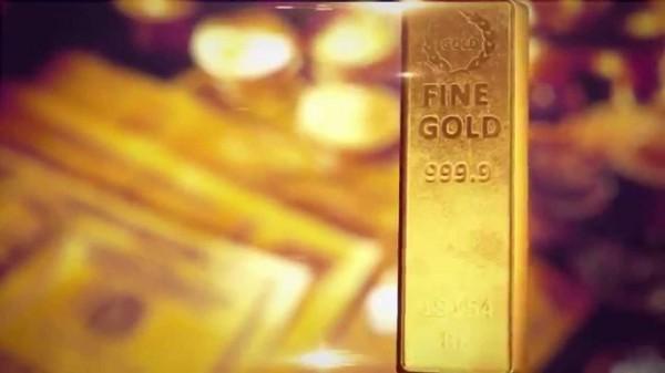 Золотой слиток на фоне купюр и монет как символы инвестиции