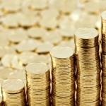 На переднем плане - аккуратные стопки золотых монет, на заднем - рассыпанные золотые монеты