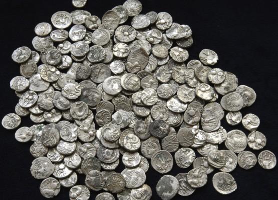 Россыпь серебряных монет на чёрном фоне