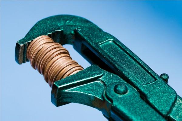 Золотые монеты в тисках на голубом фоне