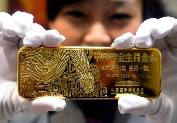 Золотой слиток в руках китаянки