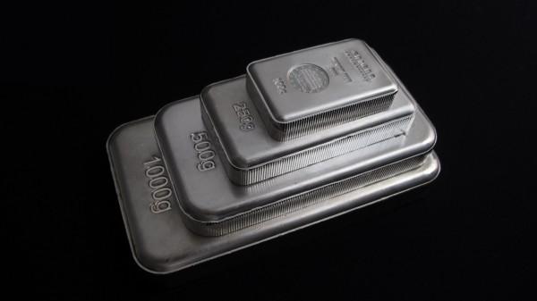 Стопка серебряных слитков на чёрном фоне