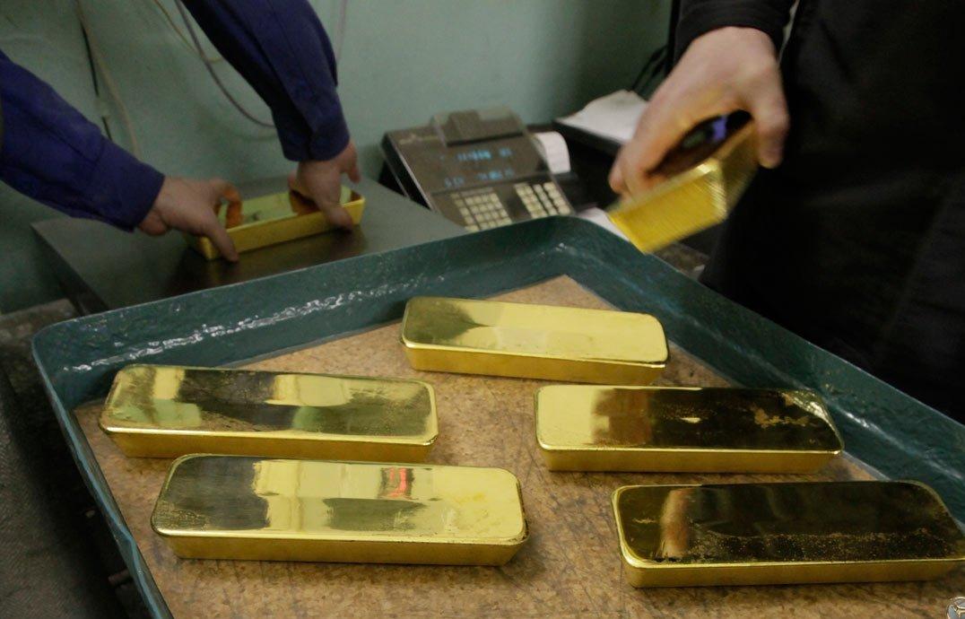 Слитки золота на стеллаже и в руках
