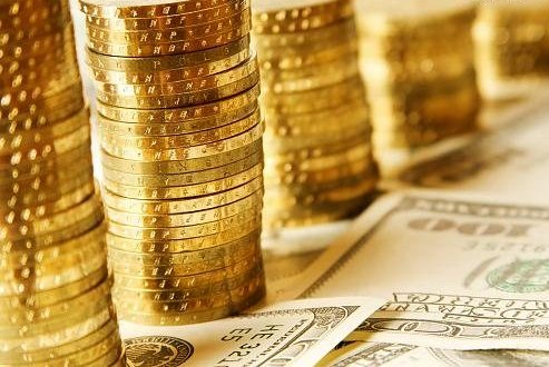 Стопки золотых монет и купюры долларов США