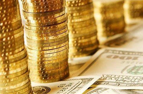 Стопки золотых монет на купюрах долларов США