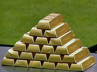 Золото: слитки на фоне газона