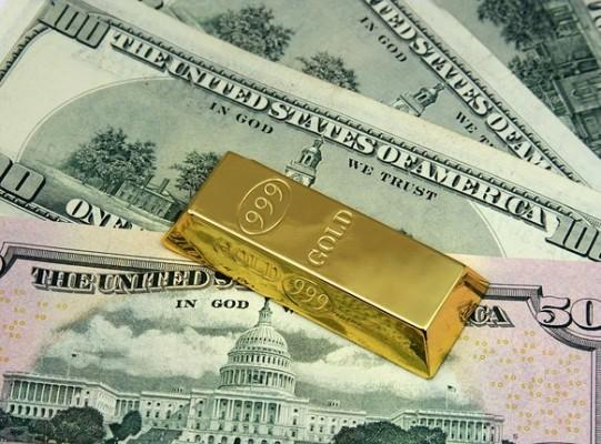 Золотой слиток на фоне купюр долларов США
