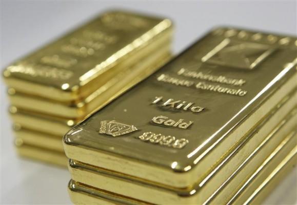 Две стопки золотых слитков на сером фоне