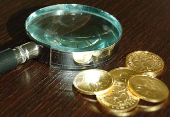 Золотые монеты и лупа