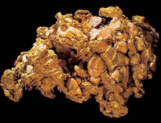 Бесформенный кусок золота на чёрном фоне