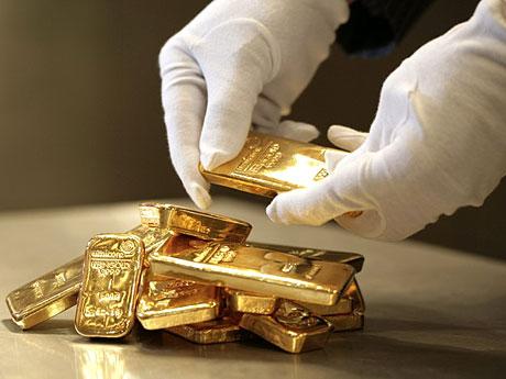 Слитки золота в руках и в стопке