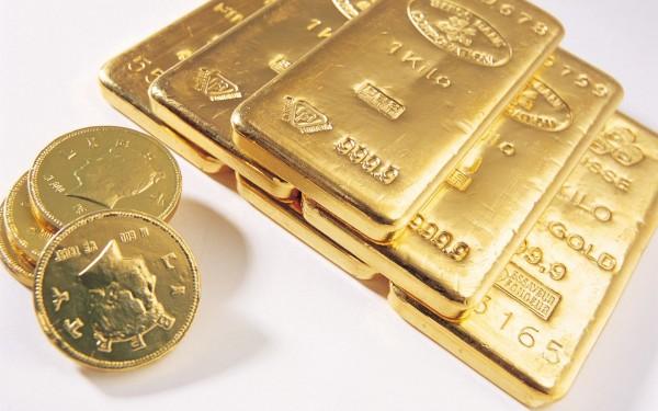 Слитки золота и золотые монеты на белом фоне