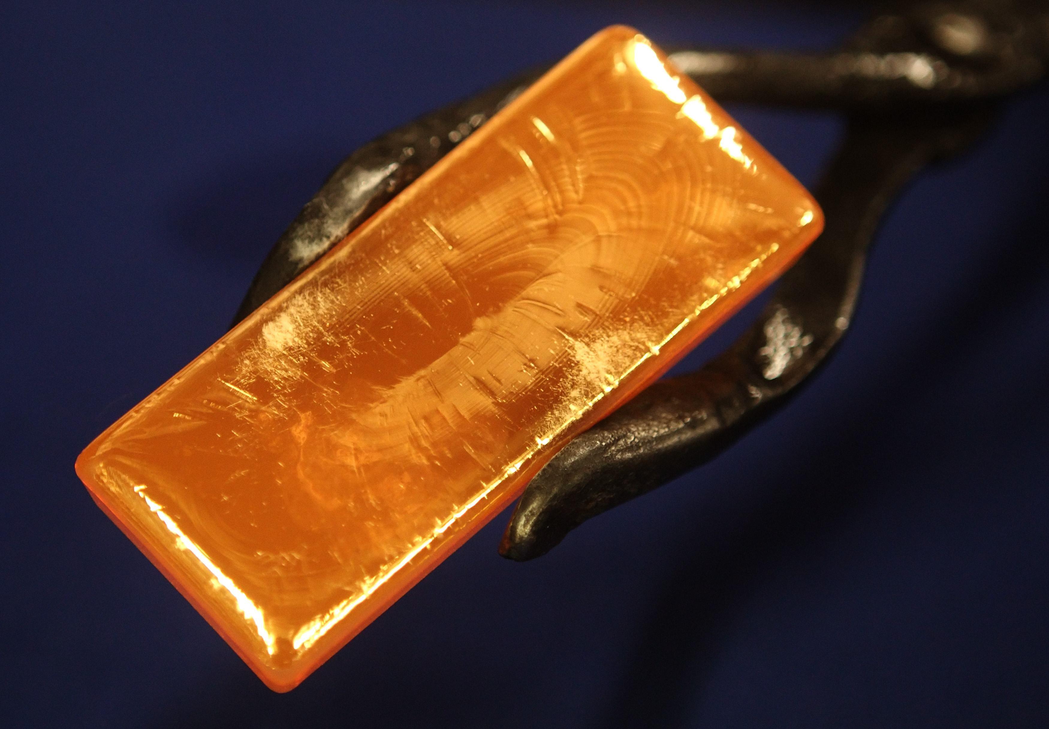 Слиток золота в щипцах