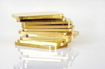 Стопка золотых слитков на сером фоне