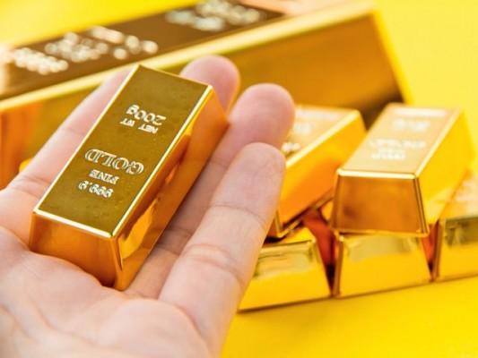 Слиток золота на руке на фоне слитков