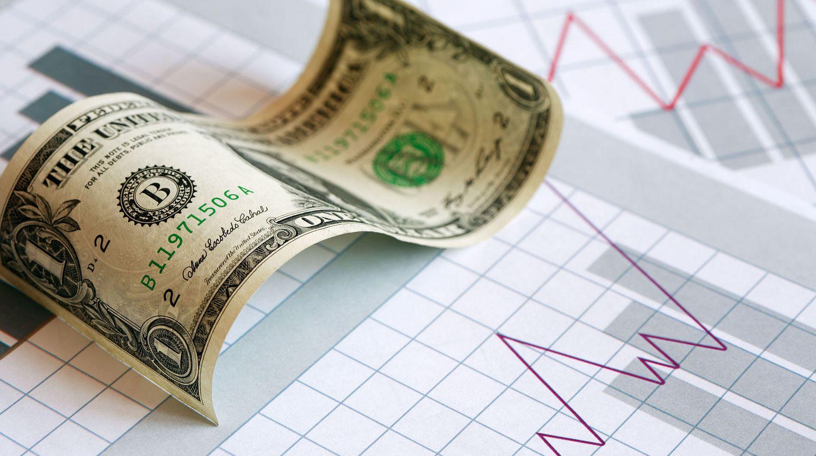 Купюра доллара США на фоне листка с графиком