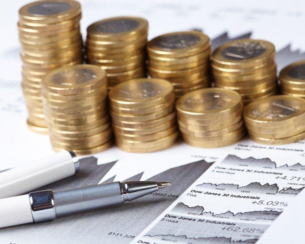 Стопки золотых монет на фоне изображений графиков и арсчётов