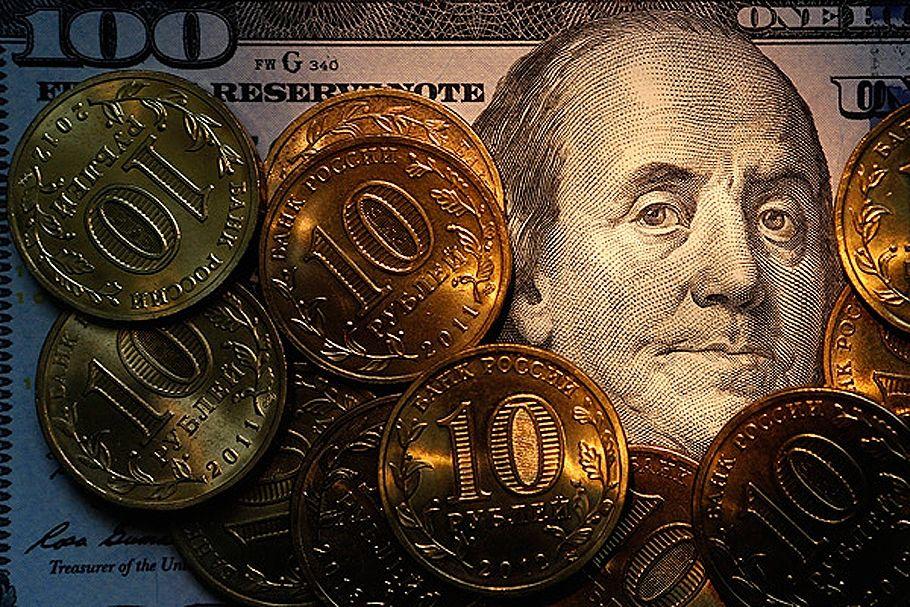 Золотые монеты на фоне стодолларовой купюры