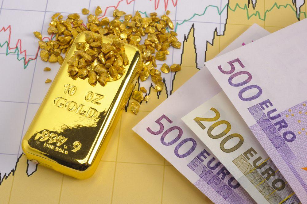 Слиток золота, россыпь золота и купюры евро на фоне графика
