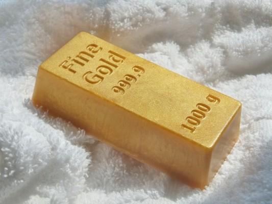 Килограммовый слиток золота на фоне белой ткани