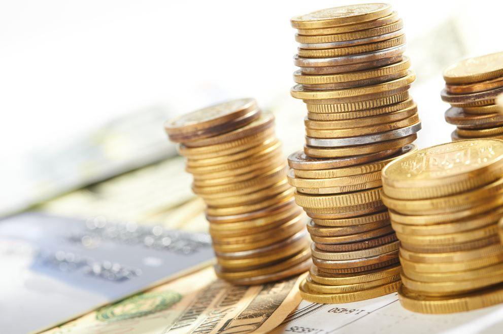 Стопки золотых монет поверх купюр долларов США