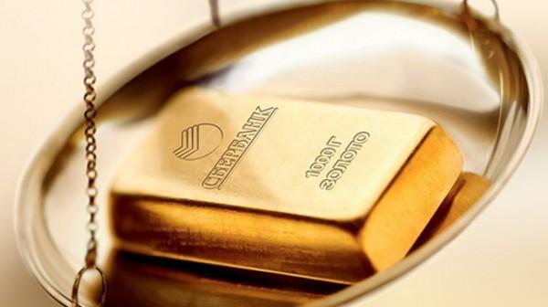Килограммовій слиток золота на весах
