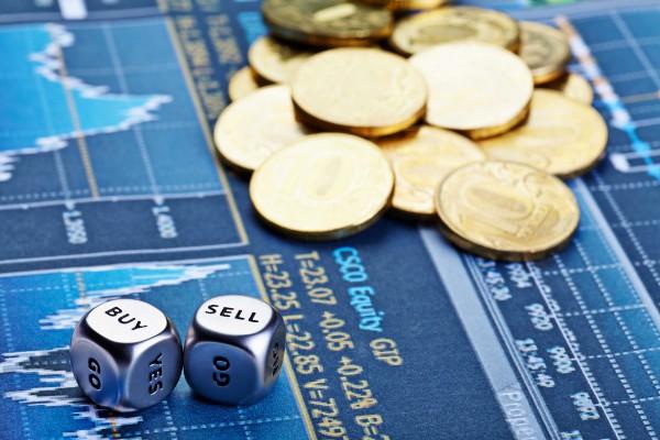 Россыпь монет и игральных костей на фоне графика