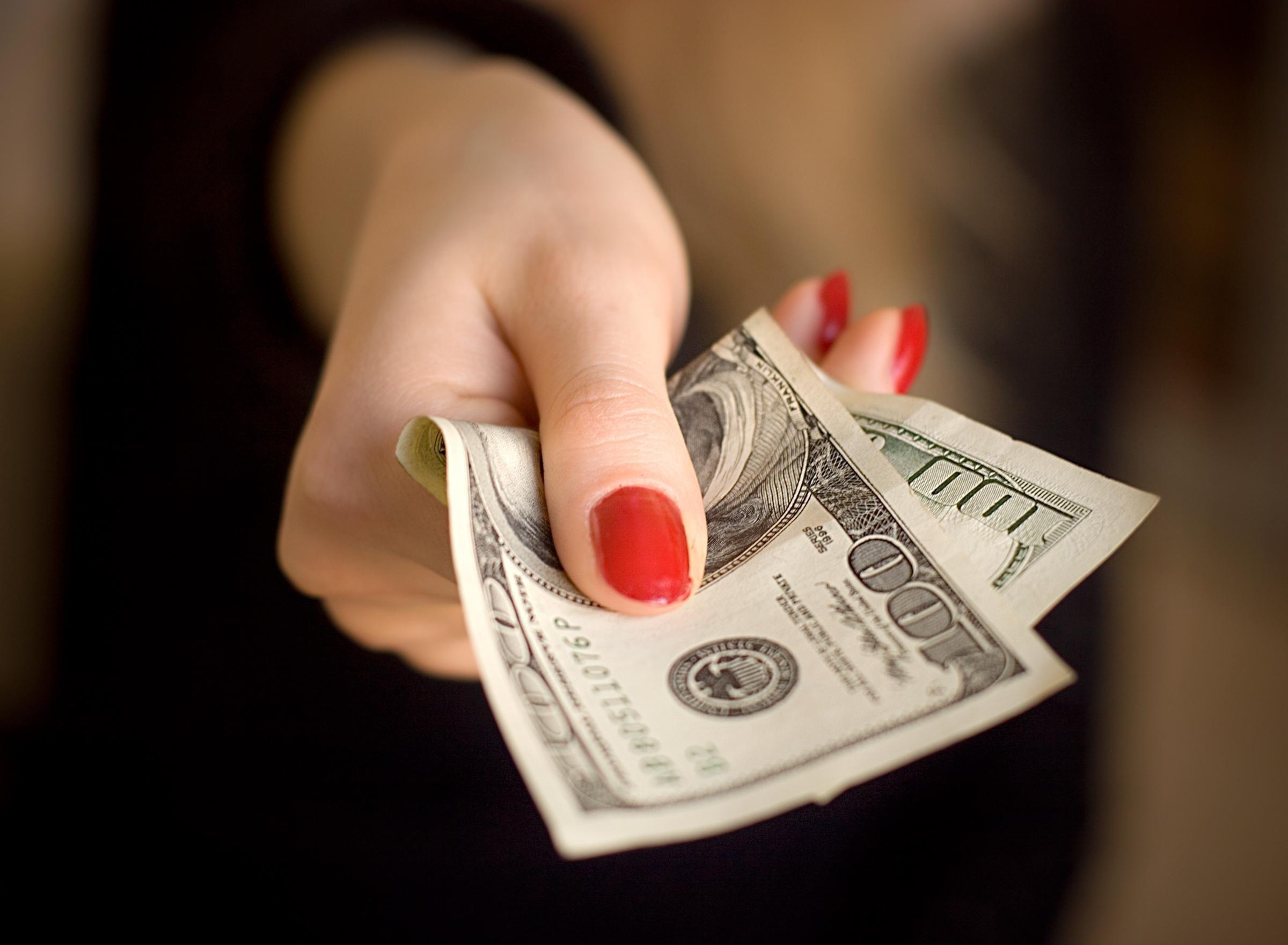 Женская рука со стодолларовой купюрой