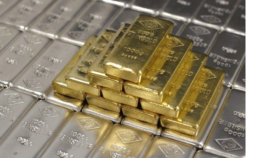 Слитки золота на фоне слитков серебра