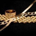 Золотые цепочки и кольцо на чёрном фоне